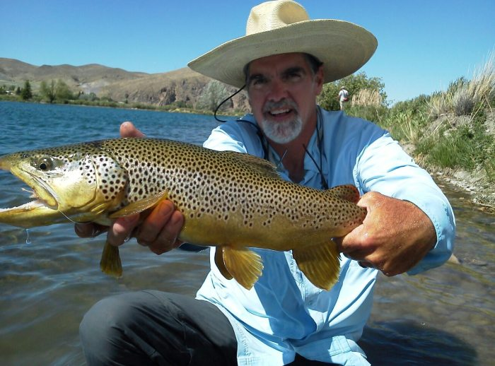 Michael Stack of FishTales Outfitting hoists a heavy Montana brown trout.